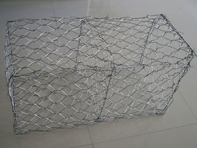 A two-cell galvanized gabion box on the floor.