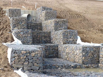 Gabion boxes are installed on the slope with a pipeline in the center of the gabion boxes.