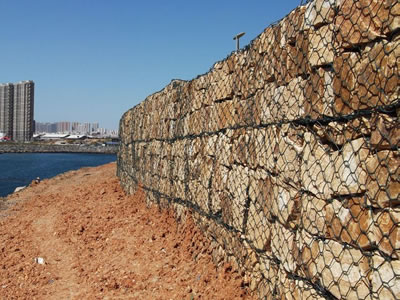 Gabion boxes with stones are installed on the seashore.