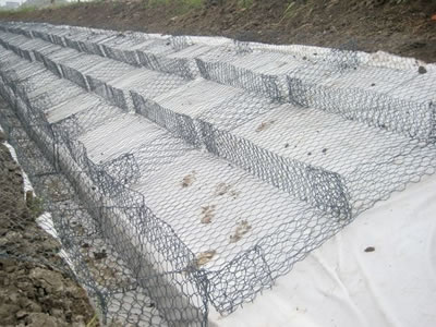 Several PVC coating gabion mattress on the slope with white geotextile under them.