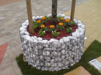 Round shape gabion planter on the ground with several flowers and three trees in it.