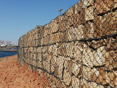 Gabion retaining walls are installed close to the river bank.