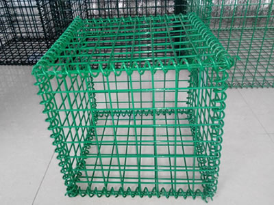 A green welded type PVC coating gabion cage on the floor.