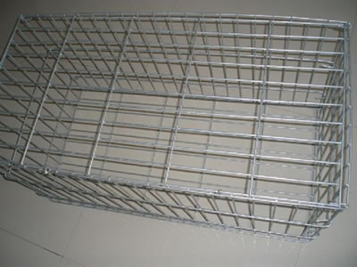 A galvanized welded gabion cage on the gray background.