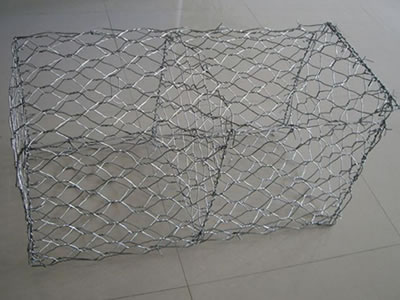 A galvanized woven gabion cage on the floor.
