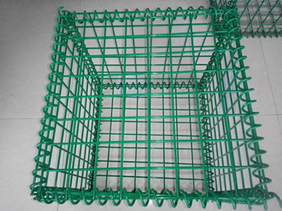 A green PVC coated welded gabion cage on the ground.