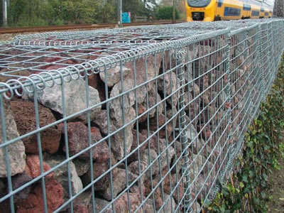 Welded gabion cages are installed on the roadside with a train driving on the railway